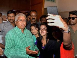 A girl takes a selfie with RJD chief Lalu Prasad