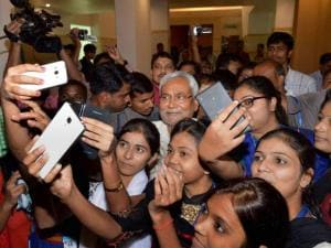Bihar Chief Minister Nitish Kumar poses for a selfie with girls
