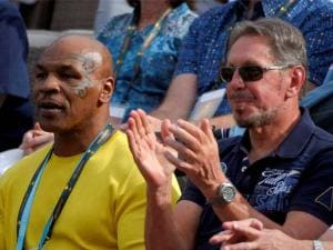 Former boxer Mike Tyson, left, and Oracle CEO Larry Ellison watch Serena Williams and Yulia Putintseva compete during their match at the BNP Paribas Open tennis
