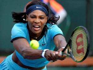 Serena Williams reaches for a shot against Yulia Putintseva during their match at the BNP Paribas Open tennis