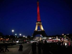 People walk towards the illuminated Eiffel Tower illuminated with the Belgium national colors black, yellow and red in honor of the victims