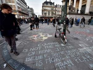 People write hundreds of messages on the asphalt at Place de la Bourse in the center of Brussels to mourn for the victims of Bomb attack