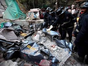 Rescue officials clear debris from the site of a collapsed building which killed a cab driver in Mumbai