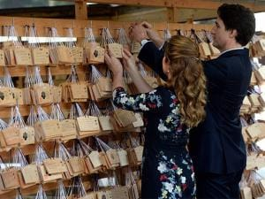 Canadian Prime Minister Justin Trudeau and wife Sophie Gregoire Trudeau hang prayer tablets during their visit to the Meiji Shrine in Tokyo