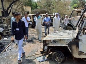People looking at the charred remains of vehicles inside Jawahar Bagh that was opened for the public