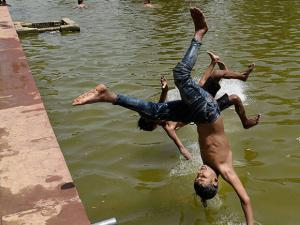 Children enjoy in the waters of a fountain to beat the heat at India Gate as the mercury rises in New Delhi