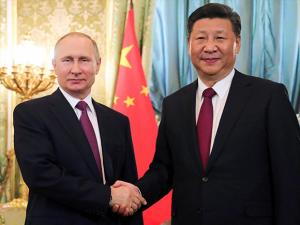 Russian President Vladimir Putin shakes hands with the Chinese President Xi Jinping