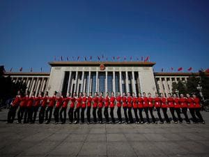 Bus ushers pose for photographs in front of the Great Hall of the People during the opening session