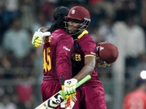 West Indies' Chris Gayle celebrates his century with Andre Russell during a ICC WT20 match against England at Wankhede Stadium