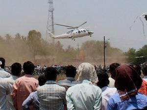 People watch as the Sikorsky VT-CMM helicopter, carrying Maharashtra chief minister Devendra Fadnavis