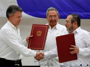 Colombian President Juan Manuel Santos and Timoleon Jimenez shake hands during a signing ceremony of a cease-fire