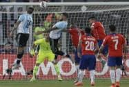 Chile's goalkeeper Claudio Bravo, center,  eyes the ball as Argentina's Marcos Rojo and Nicolas Otamendi