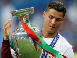 Portugal's Cristiano Ronaldo walks with the trophy at the end of the Euro 2016 final