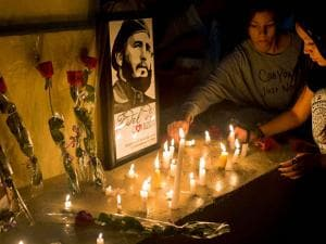 Students place candles around an image of the late Cuban leader Fidel Castro