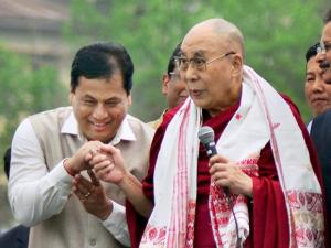 Tibetan spiritual leader Dalai Lama shaking hands with Assam Chief Minister Sarbananda Sonowal