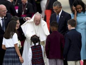 Pope Francis greets children as he is escorted by President Barack Obama