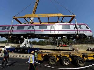 A crane being used to lower a Metro train on the tracks on Magenta Line