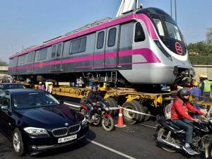 A trailer caries a Metro train to the tracks as DMRC unloaded the first six coach train for the trial on its Magenta Line