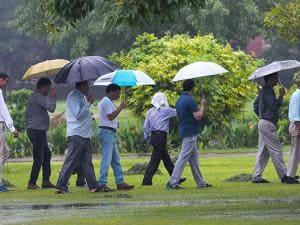 Peoples hold umbrellas to protect themselves   during the  monsoon rains in New Delhi