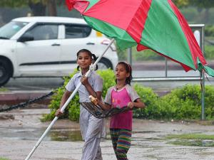 Street vendors hold umbrella to protect themselves  during the  monsoon rains in New Delhi