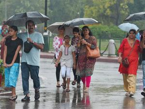 Tourists hold umbrellas to protect themselves   during the  monsoon rains