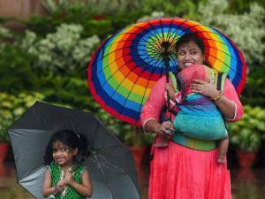 Tourists pose for photo  during the  monsoon rains in New Delhi