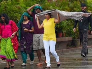 Tourists protect themselves as they enjoy monsoon rains in New Delhi
