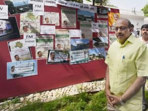 BJP MP Vijay Goel near a signboard with cuttings of AAP goverment's alleged hyper-publicised advertisements on odd-even rule, at his residence in New Delhi