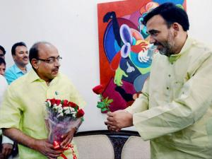 Delhi Transport Minister Gopal Rai presents rose to  BJP MP Vijay Goel who violated the odd-even rule as a mark of protest against the scheme in New Delhi
