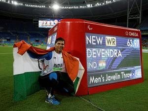 Devendra Jhajharia poses for the pictures next to the scoreboard that shows his world record
