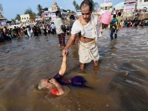 An old woman taking holy bath at the Kumbakonam Mahamaham pond on the occasion of the Mahamaham festival 2016 in Kumbakonam