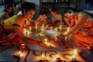 Young girls light earthen lamps Diwali festival celebration