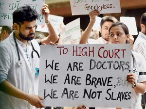 Resident doctors show placards during a protest rally at the KEM hospital