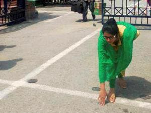 Indian woman Uzma touching the ground after entering the Indian territory via Attari-Wagah border