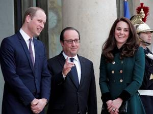 French President Francois Hollande gestures as he welcomes Prince William with Kate, Duchess of Cambridge, at the Elysee Palace in Paris