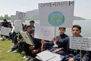 School children hold placards sitting on the banks of Dal Lake to mark World Earth Day in Srinagar