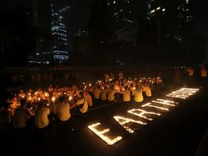 Activists light candles and hold torches as buildings turn their exterior lights off for the Earth Hour in Jakarta, Indonesia