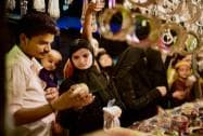 A couple looks at a imitation jewelery at a road side night market  ahead of Eid-ul- Fitr