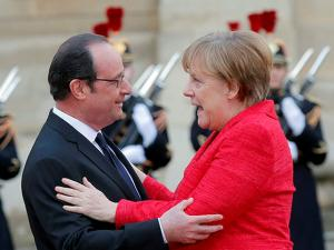 French President Francois Hollande greets German Chancellor Angela Merkel prior to their meeting at the Versailles castle near Paris