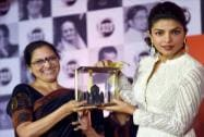 Social worker Meera Badve offers a memento to Bollywood actress Priyanka Chopra