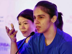 Ace shuttler Saina Nehwal speaks as boxer Mary Kom looks on at a felicitation function for particiapnts of World Winter Games 2017