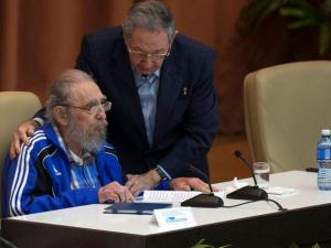 Cuba's President Raul Castro, right, embraces his brother Fidel as he leans over to speak with him during the last day of the 7th Cuban Communist Party Congress in Havana, Cuba