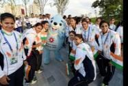 Indian athletes pose with the official mascot of the games during the flag hoisting ceremony