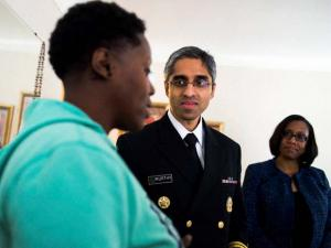 Surgeon General Vivek Murthy listens to Flint resident Tia Simpson at her home on Flint's south side
