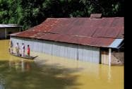 A family shifting to safer place by a boat in flood affected Teok