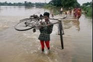 A villager walks through a submerged road lifting his bicycle the flood affected Buraburi