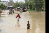 People wade through a flooded road in Barabakni district