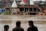 People watching the submerged Hanuman Temple caused due to flood on the banks of River Jhelum in Sinagar