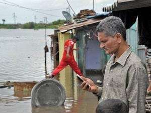 A man checks weather forecast on his cell phone in front of submerged houses after heavy rains in Koyna dam's catchment area in Sangli