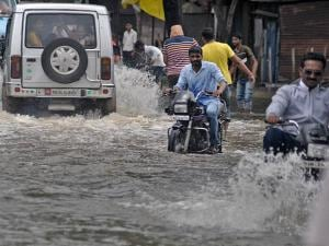 Commuters wade through a waterlogged road after heavy rains in Koyna dam's catchment area in Sangli